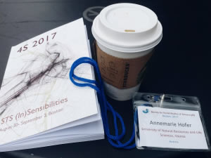 Photograph of a cup of coffee, 4S 2017 program, and conference badge