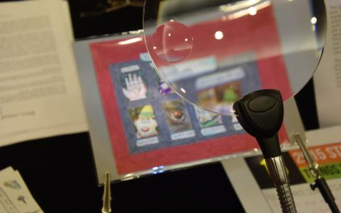 A close up of a magnifying glass directed at a blurry colorful drawing being held in place by small corner clips. The blurry card has a red border and a series of small images arranges in two rows.