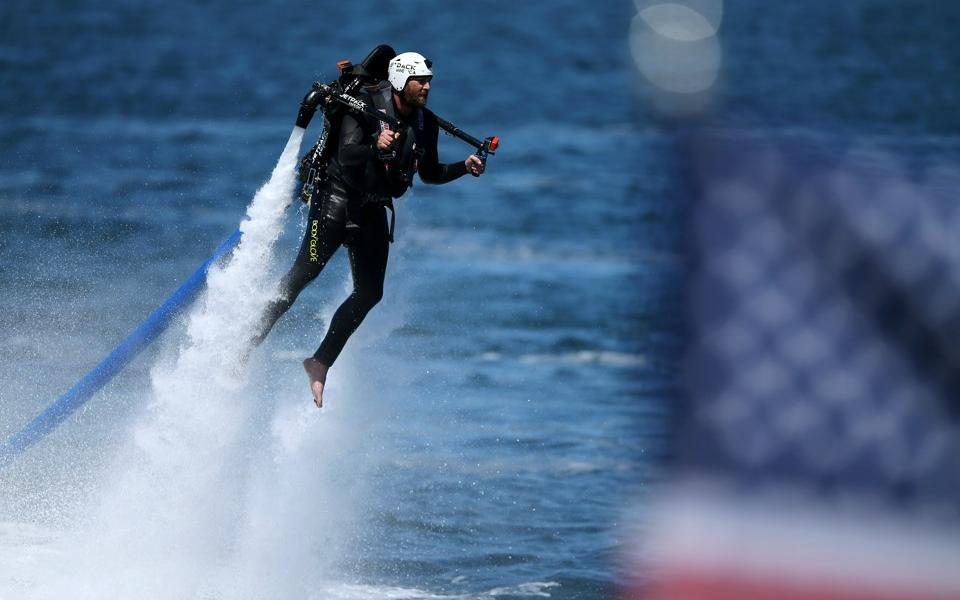 Mike Blake / Reuters. Damien Burch shoots out of the water on a jetpack during an event to help U.S. military veterans in September 2016.